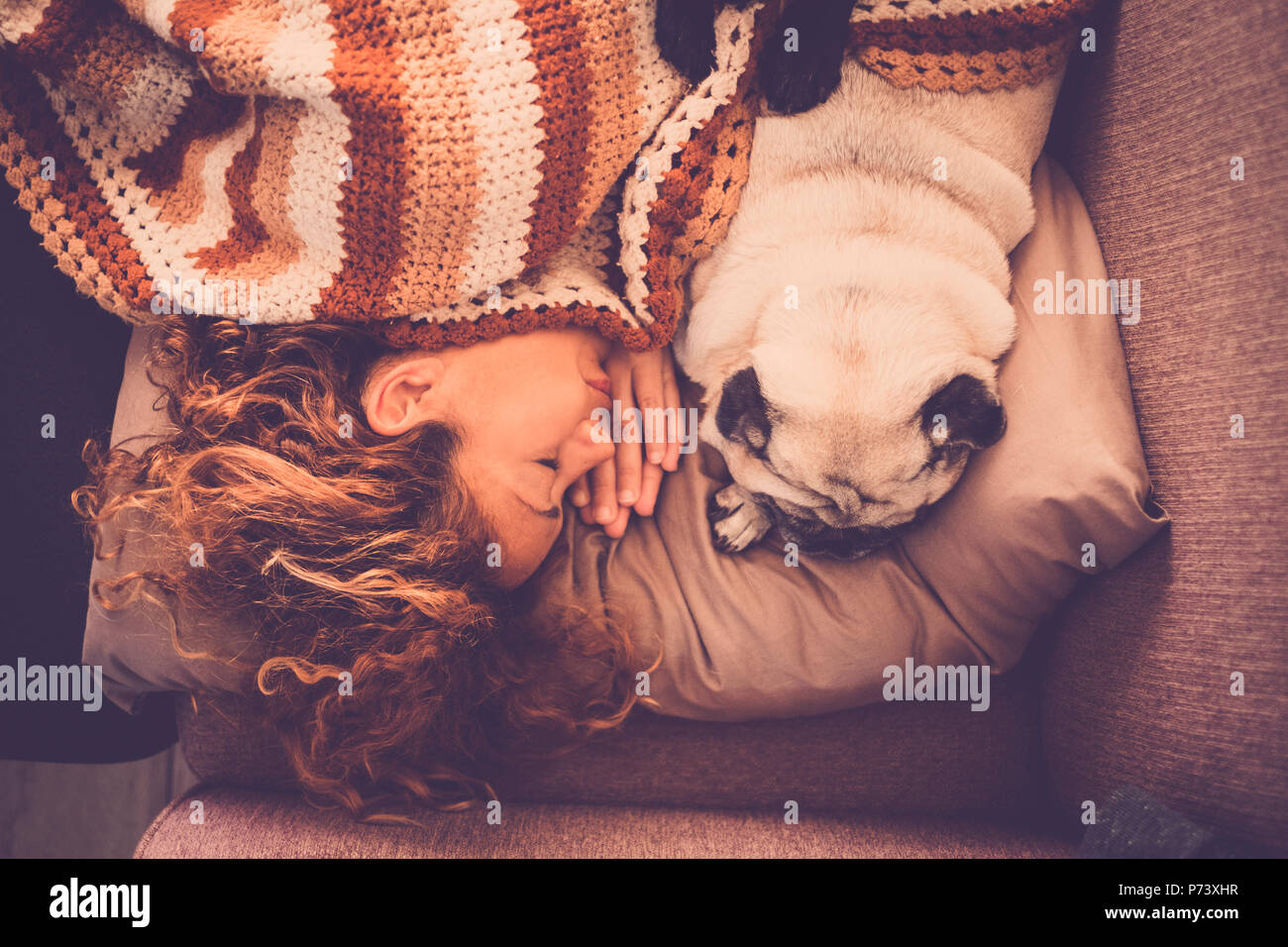 lovely couple woman pug dog sleep together at home in a tender and sweet romantic scene. staying closer with love and friendship. true relationship be - Stock Image