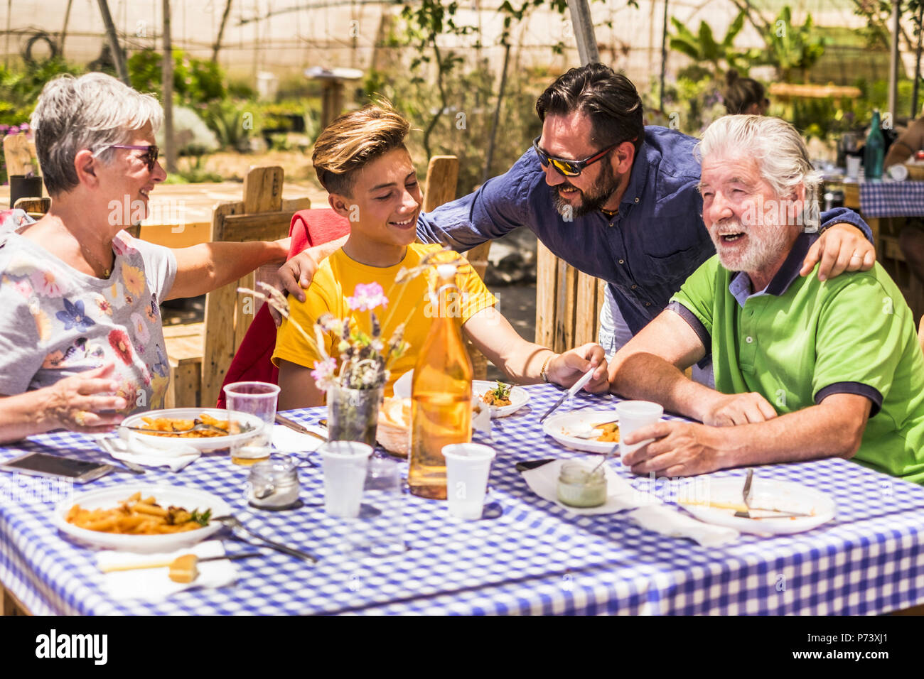 family caucasian people having lunch in natural alternative restaurant all together with joy and fun. smiling and laughing three different generations - Stock Image