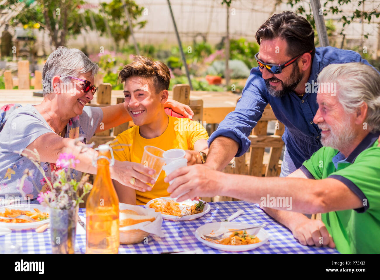 family three differente grnarations grandfathers father son all together celebrating the nice summer weather in outdoor leisure activity in an alterna - Stock Image