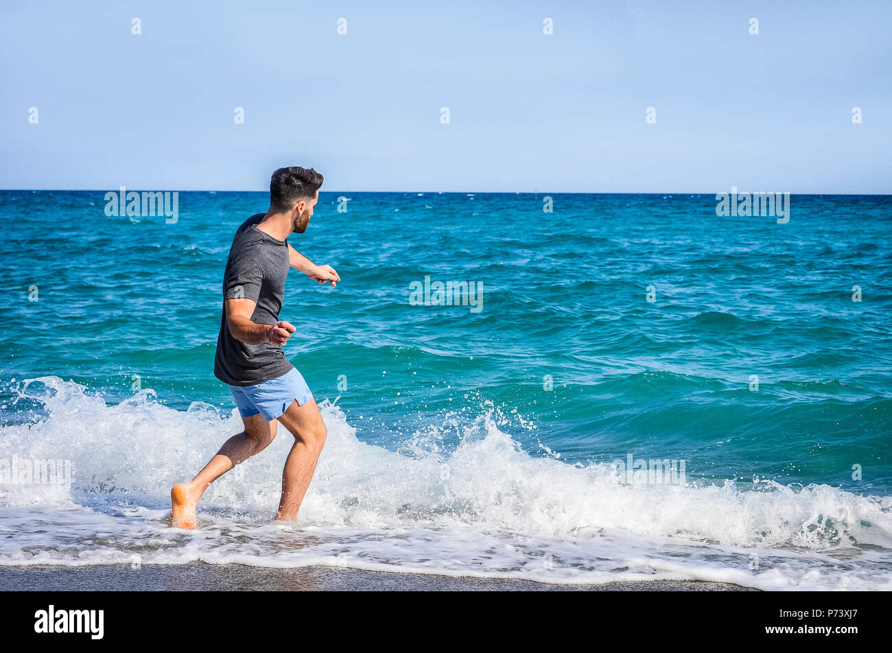 Young Man on Beach Skipping Stones on Sea - Stock Image