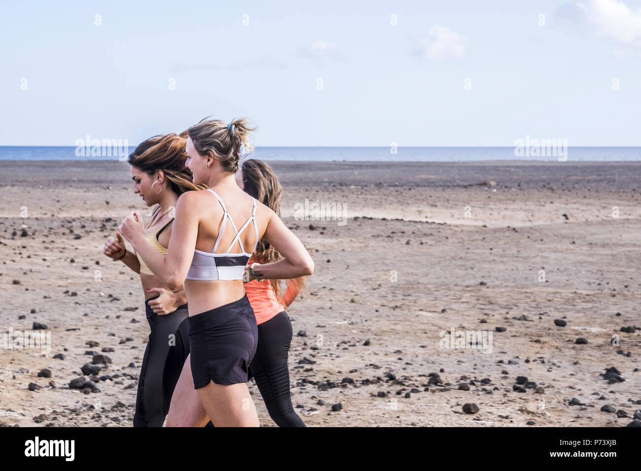 three caucasian beautiful young ladies running near the ocean on the beach for healthy positive lifestyle and carefree. happy to work on body results  - Stock Image