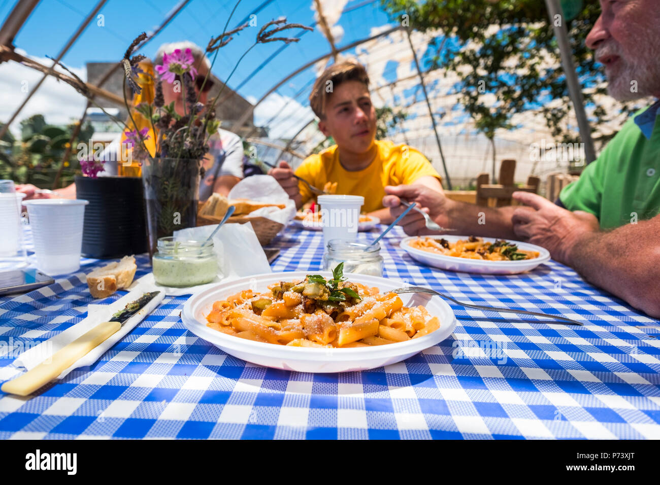 close up of pasta alla norma italian typical food. family caucasian people enjoying an alternative restaurant in the nature outdoor. all bio and veget - Stock Image