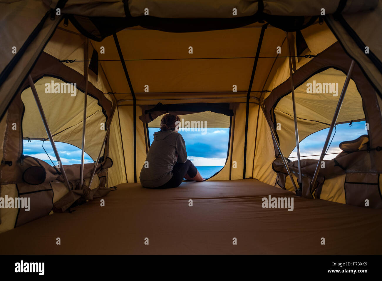 lonely independent strong middle age woman feeling the nature outdoor in a roof tent on the car. travel and lifestyle wanderlust concept for beautiful - Stock Image