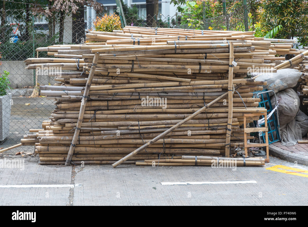 Big Stacks of Bamboo Sticks Poles at Construction Site - Stock Image