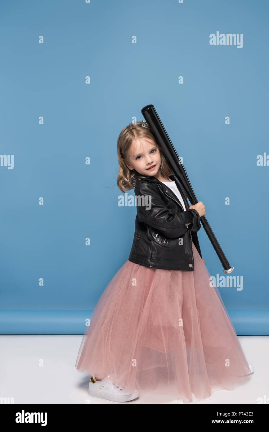 Cute little girl in leather jacket and pink skirt holding baseball bat and smiling at camera Stock Photo