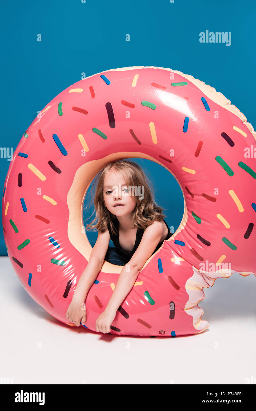 adorable little girl sitting at swimming tube in shape of doughnut - Stock Image