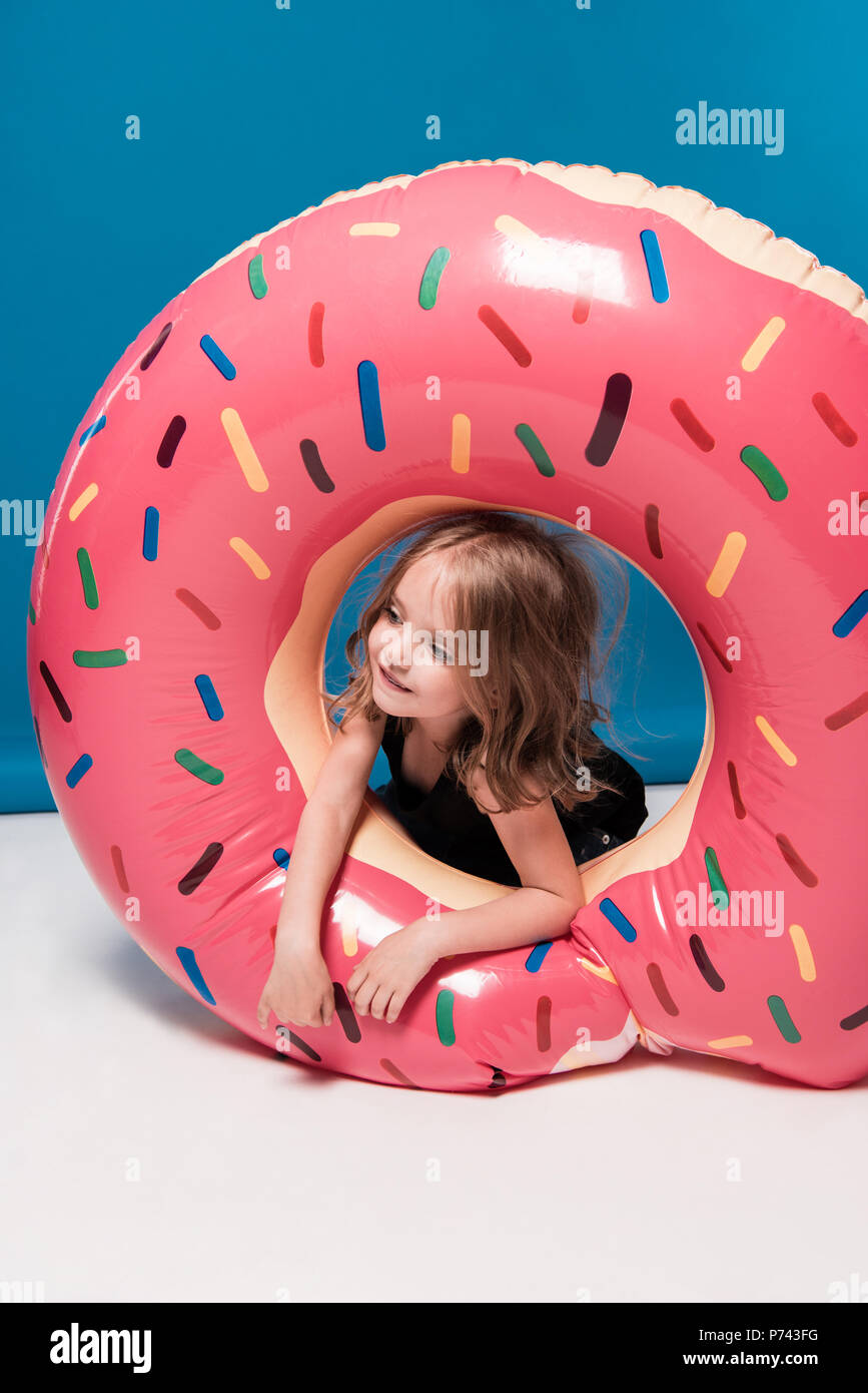 adorable little girl playing with swimming tube in form of doughnut - Stock Image