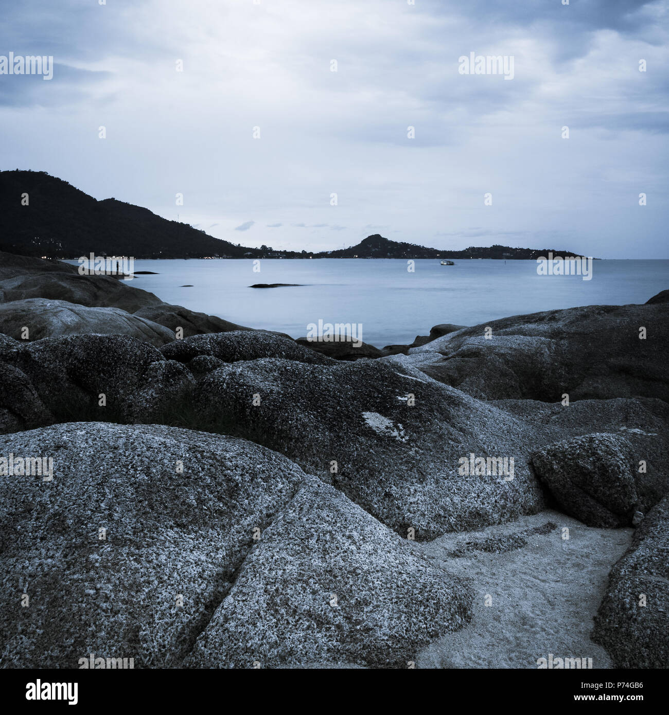 Rocky seashore with distant land. Silver tint - Stock Image