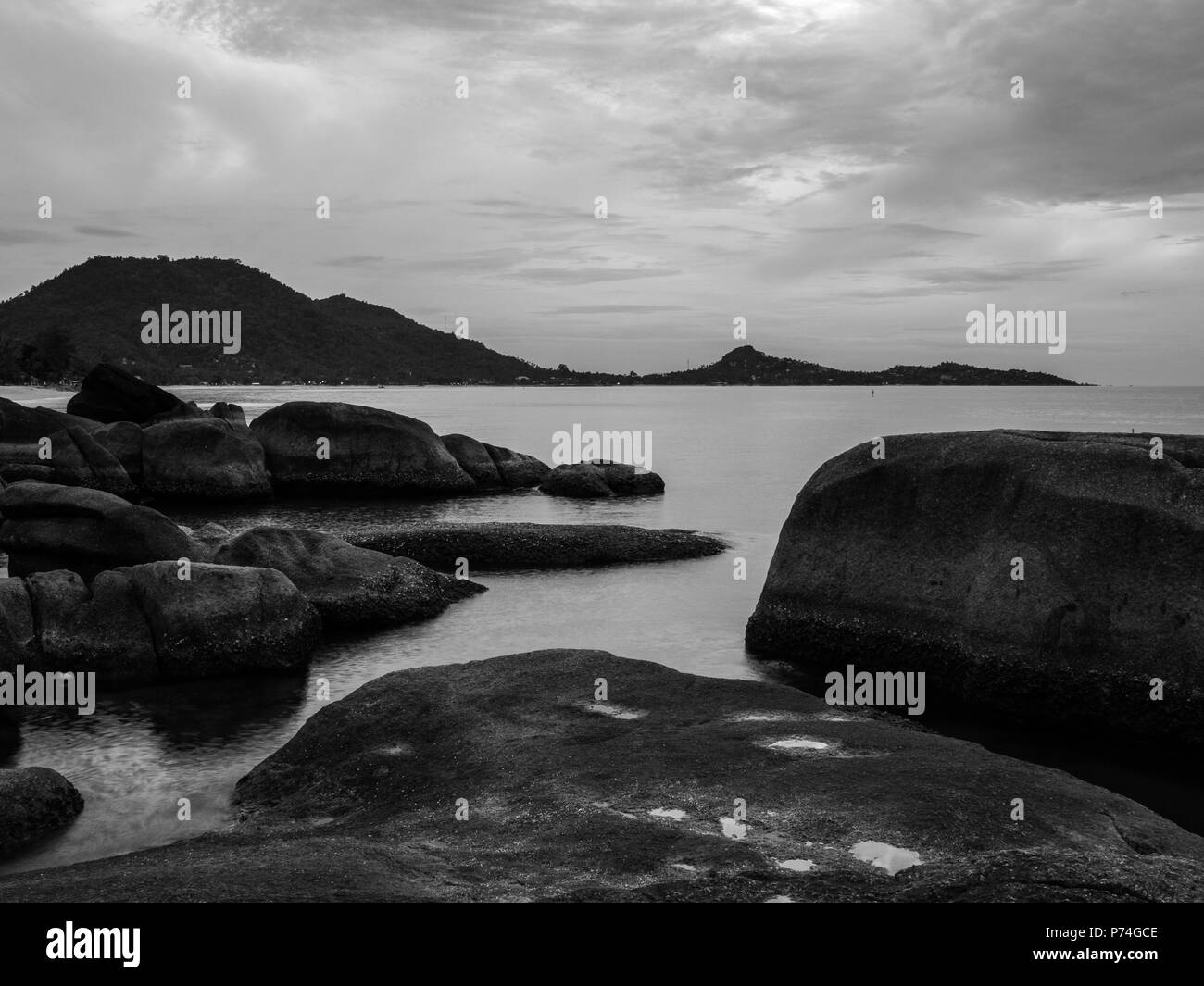 Large rocks near sea shore with the distant land. Black and white - Stock Image