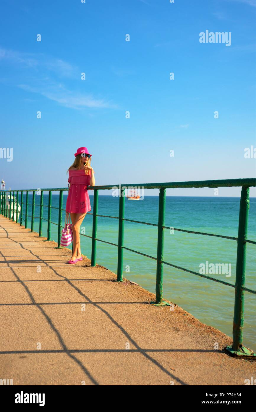 Young girl in pink sundress and with handbag standing on a pier leaning on a green fence admires summer sea - Stock Image