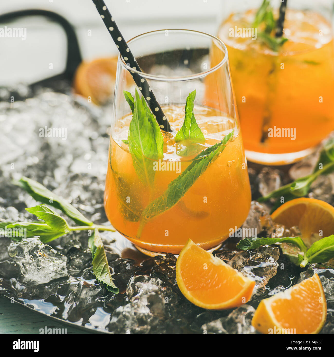 Refreshing cold alcoholic summer citrus cocktail with orange, peppermint and ice in stemless glasses on dark tray over light blue wooden table backgro - Stock Image