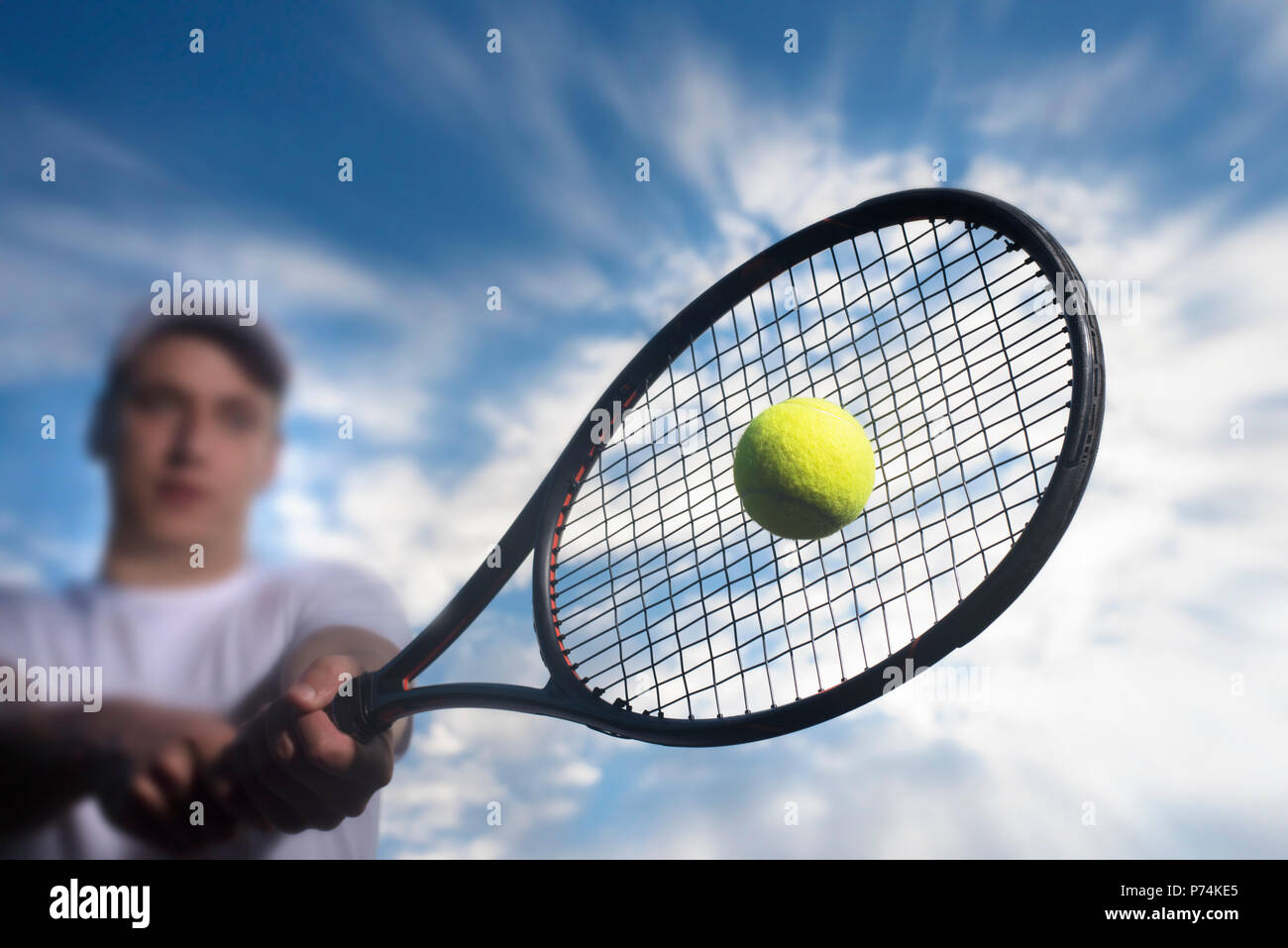 Tennis player hitting ball with backhand - Stock Image