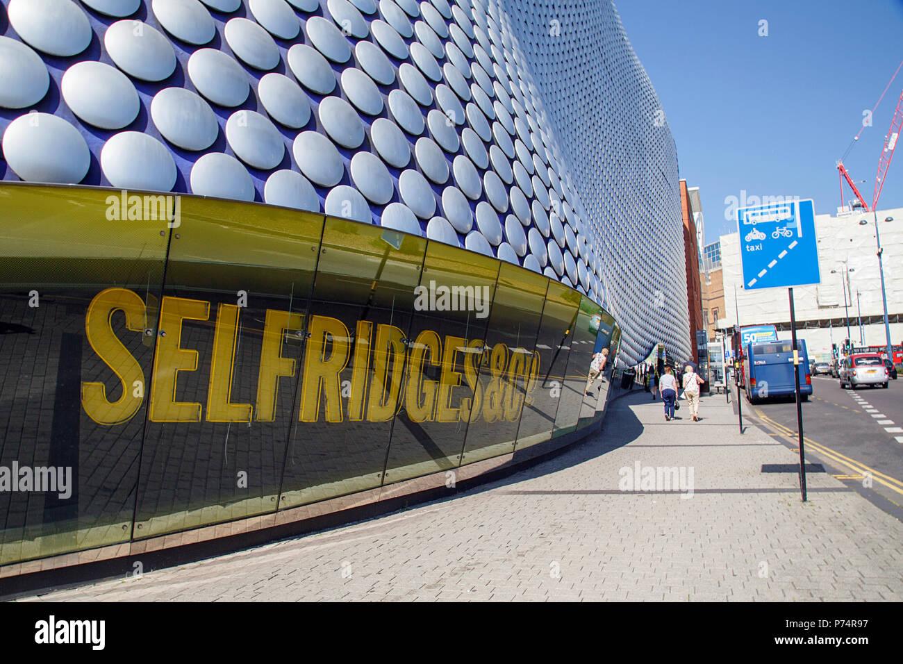 Birmingham, UK: June 29, 2018: Selfridges Department Store in Park Street - part of the Bullring Shopping Centre. Pedestrians walk toward the bus stop - Stock Image