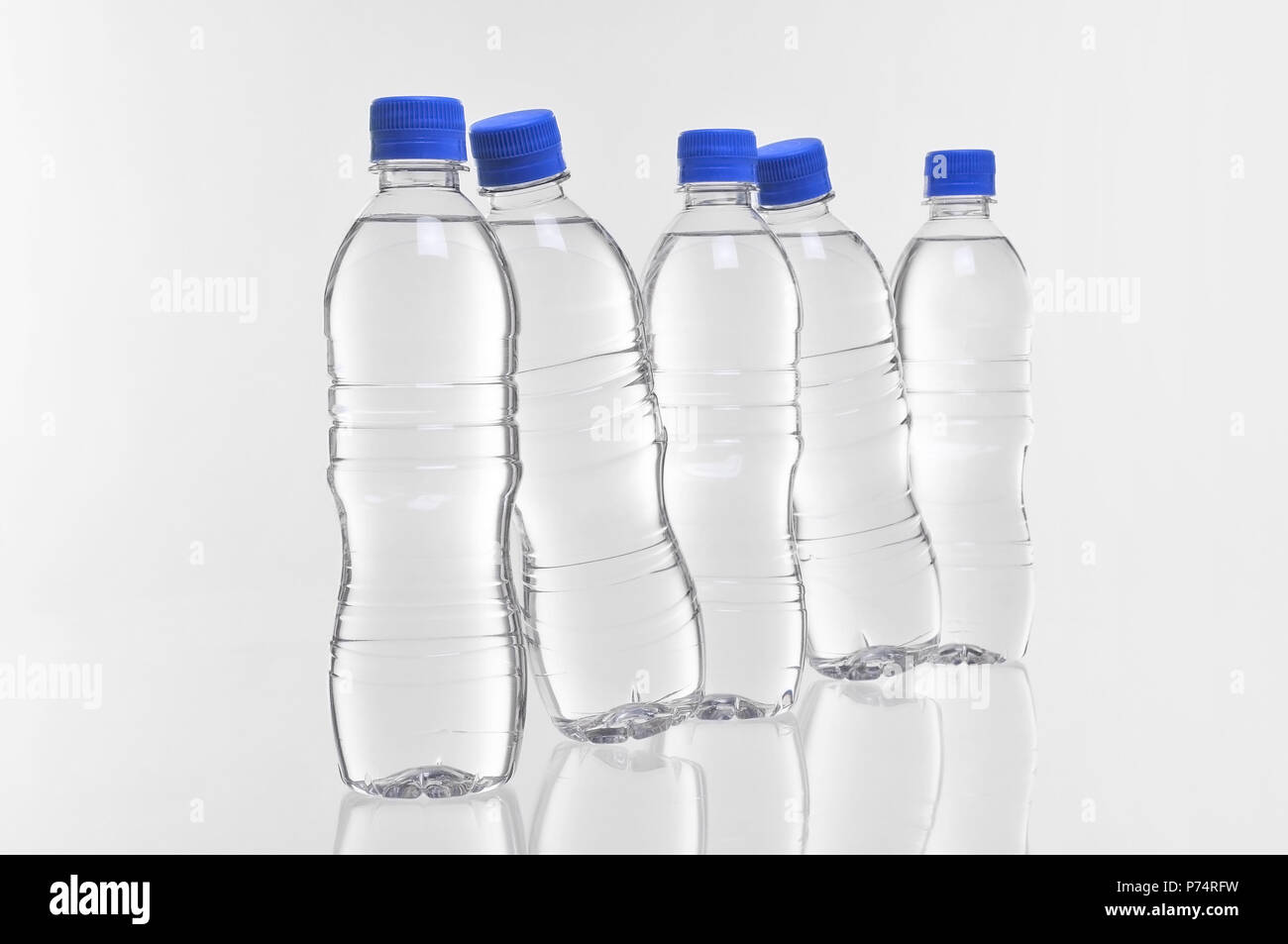 five plastic water bottles with two at an angle - Stock Image