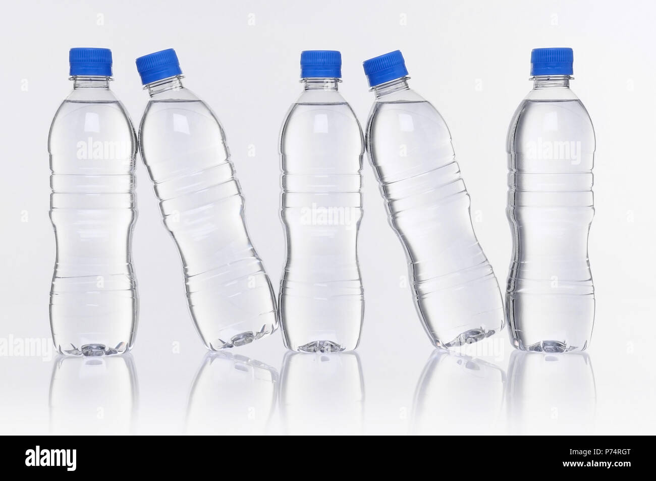 row of five plastic water bottles with reflection - Stock Image