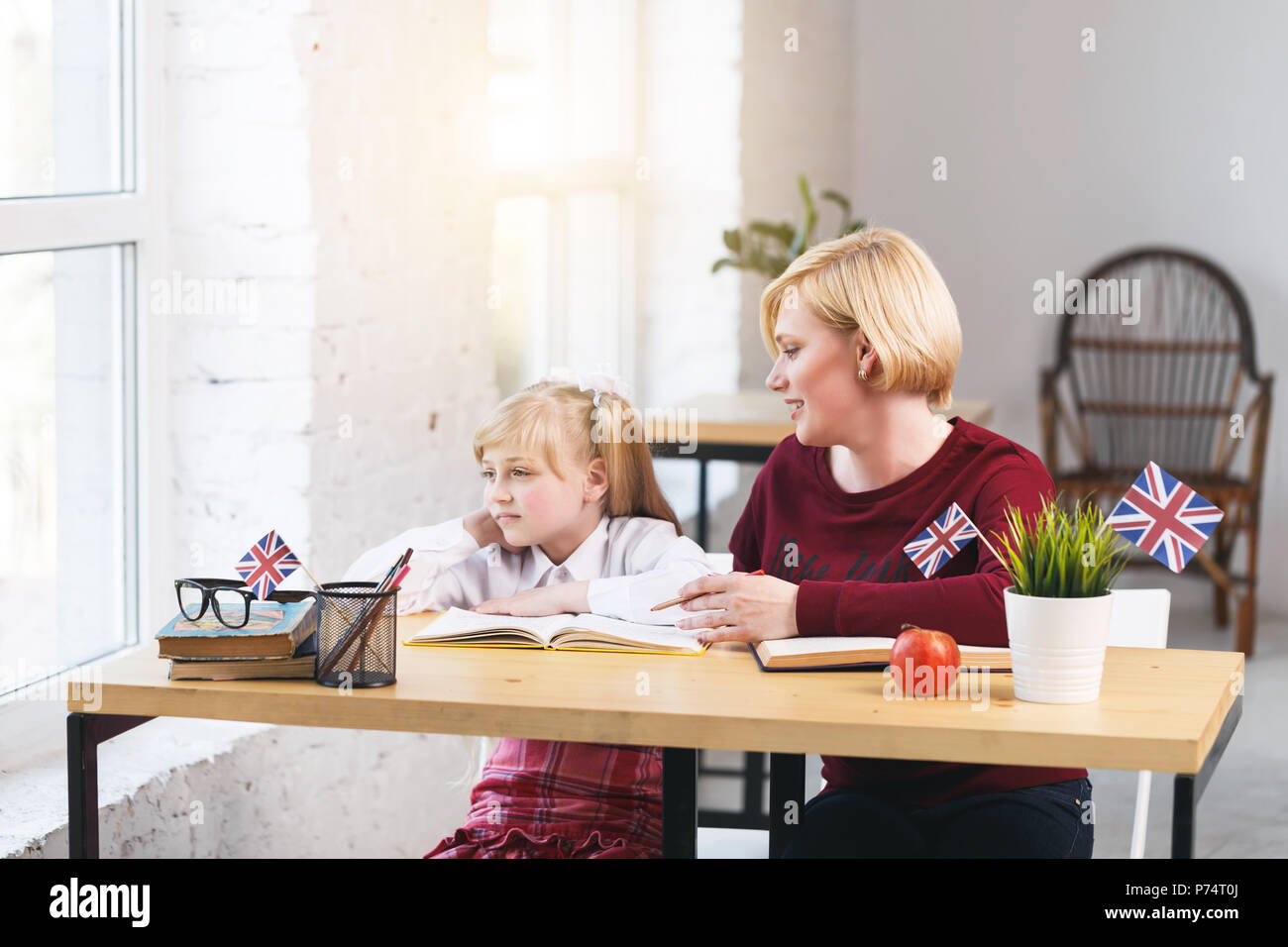 Female educator of English and tired girl, working table with books, british flag and apple, kids education language concept - Stock Image