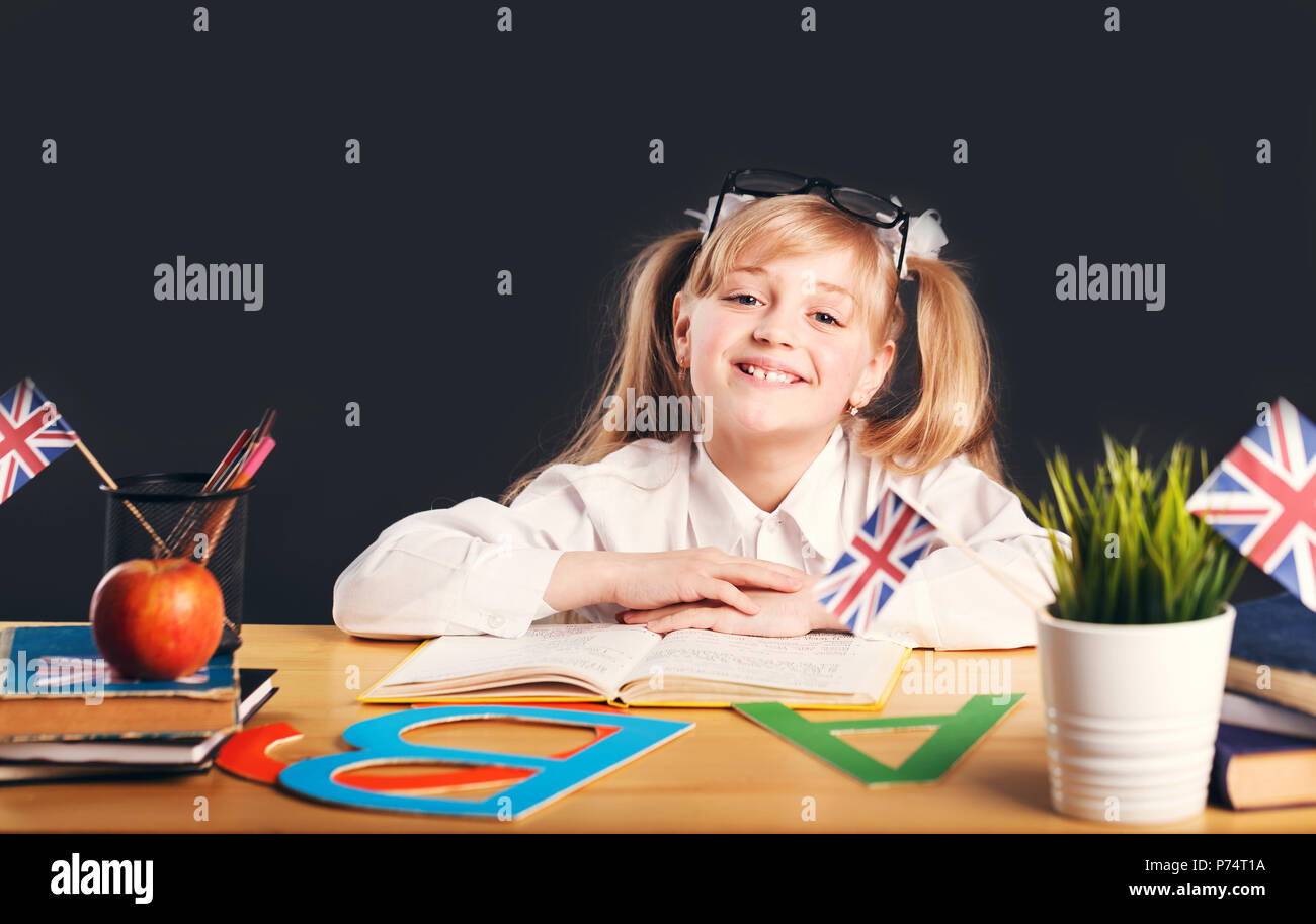 Happy smiling girl learning English language with book before dark background - Stock Image