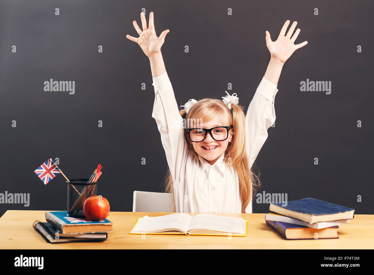 Young pupil girl wears smart eyeglasses rise hands up learning English language with book before dark background - Stock Image
