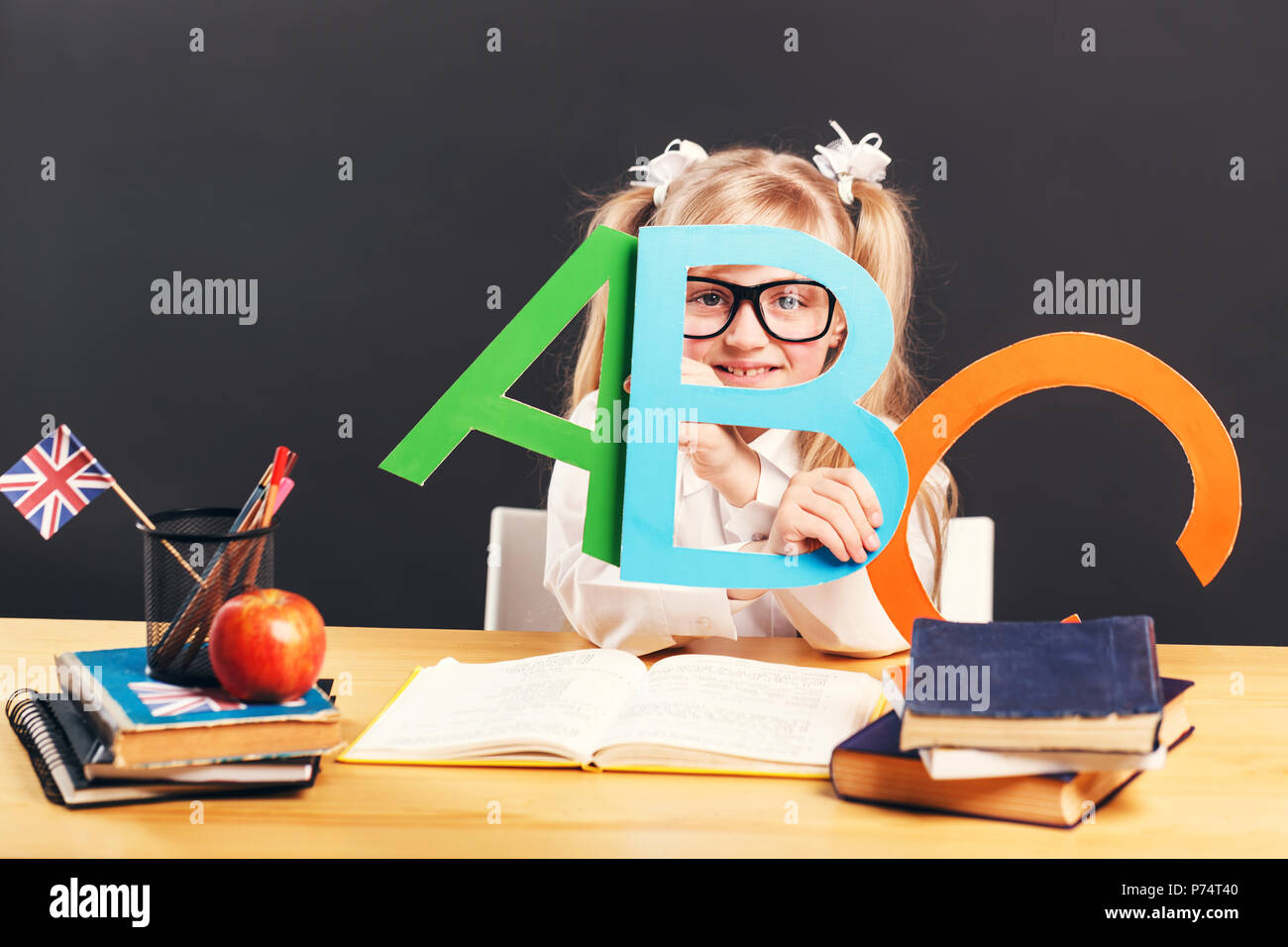 Young pupil girl wears smart eyeglasses holding colorful letters while learning English language with book before dark background - Stock Image