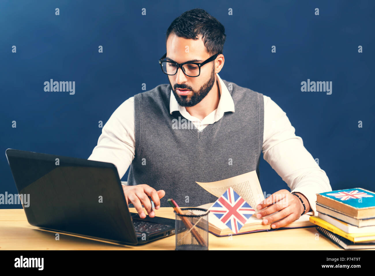 Black-haired man learning english, wearing gray sweater vest and pristine white shirt, working hard at the office desk with laptop before black wall - Stock Image