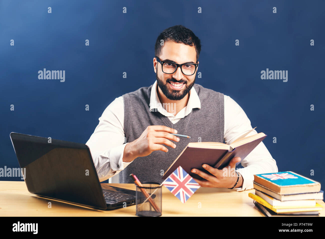 Black-haired bearded man learning english, wearing gray sweater vest and pristine white shirt, working hard at the office desk with laptop before black wall - Stock Image