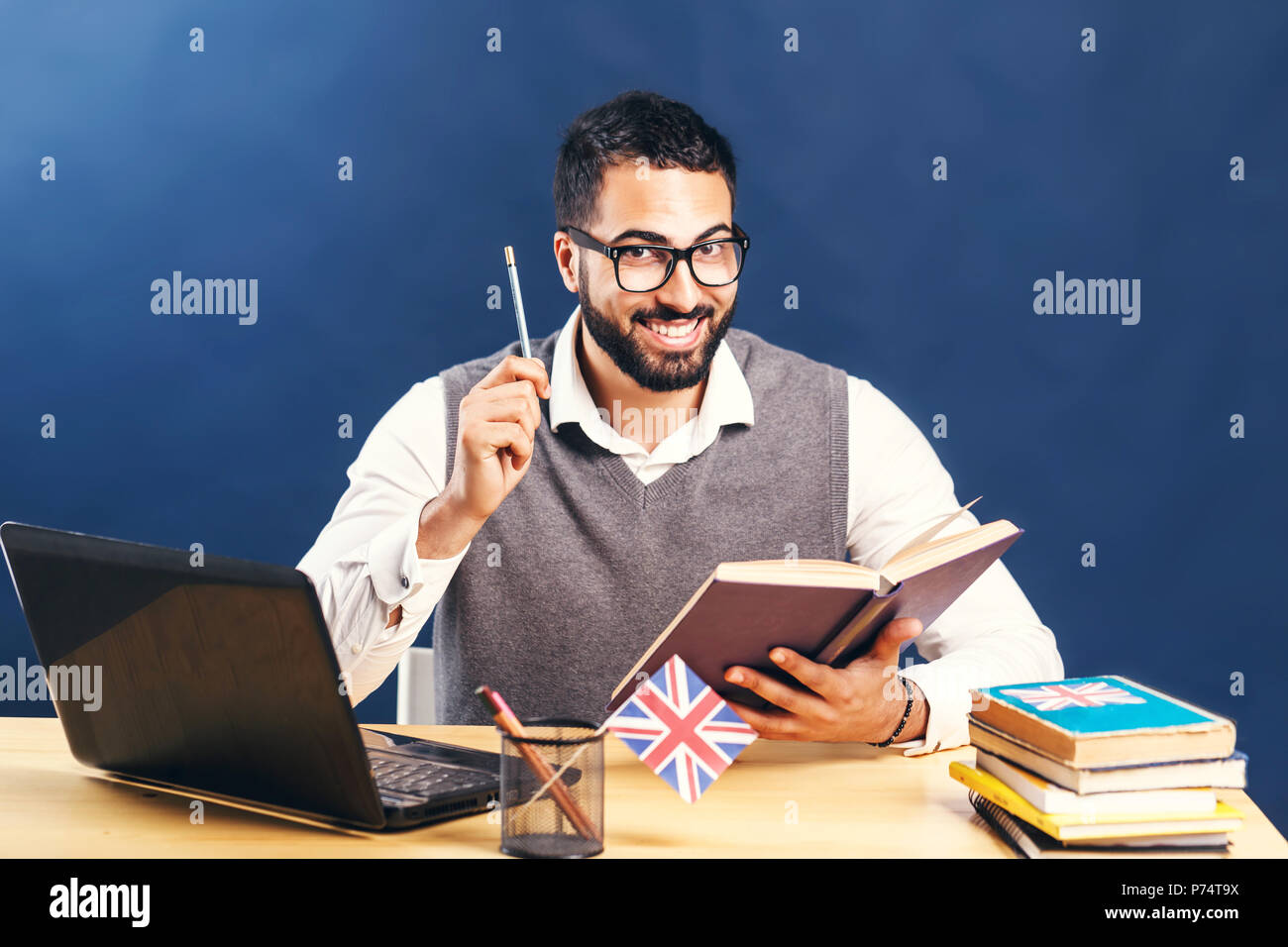 Black-haired man learning english, wearing gray sweater vest and pristine white shirt, smiling at the office desk with laptop before black wall - Stock Image