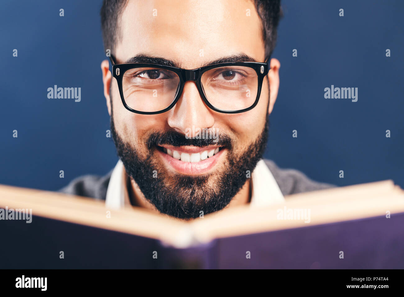 Portrait of eastern arab bearded man reading book before blue background - Stock Image