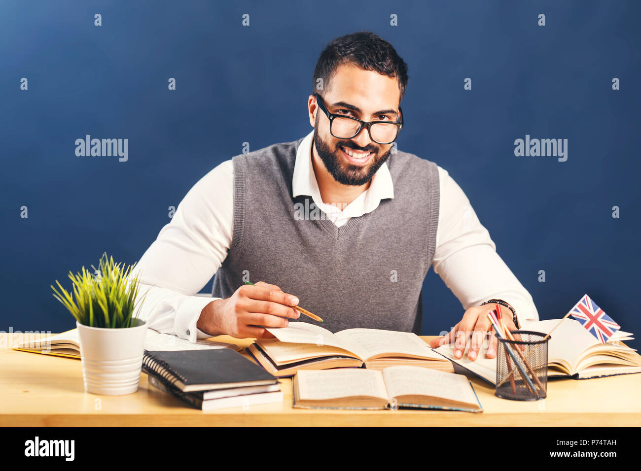 Eastern bearded man working hard learning english, wearing gray sweater vest and pristine white shirt, office desk before black wall - Stock Image