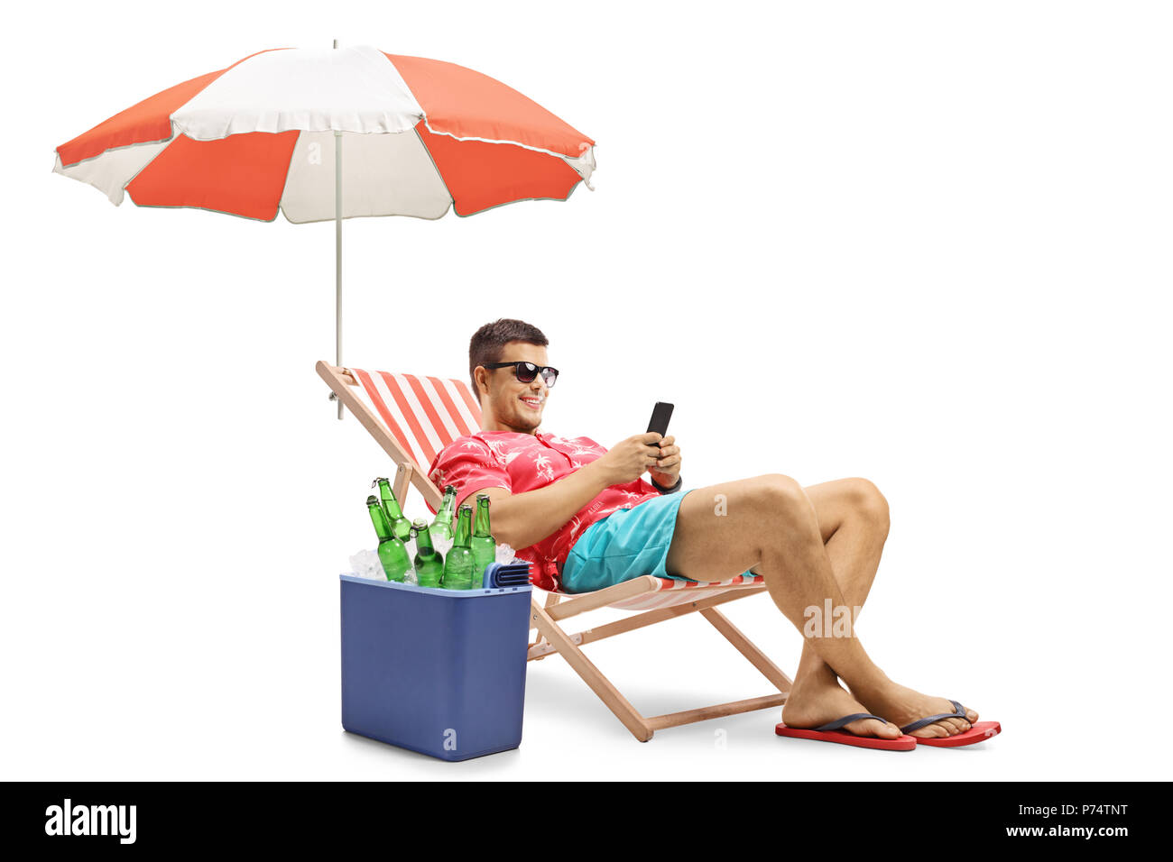 Tourist with a phone sitting in a deck chair with an umbrella next to a cooling box isolated on white background - Stock Image