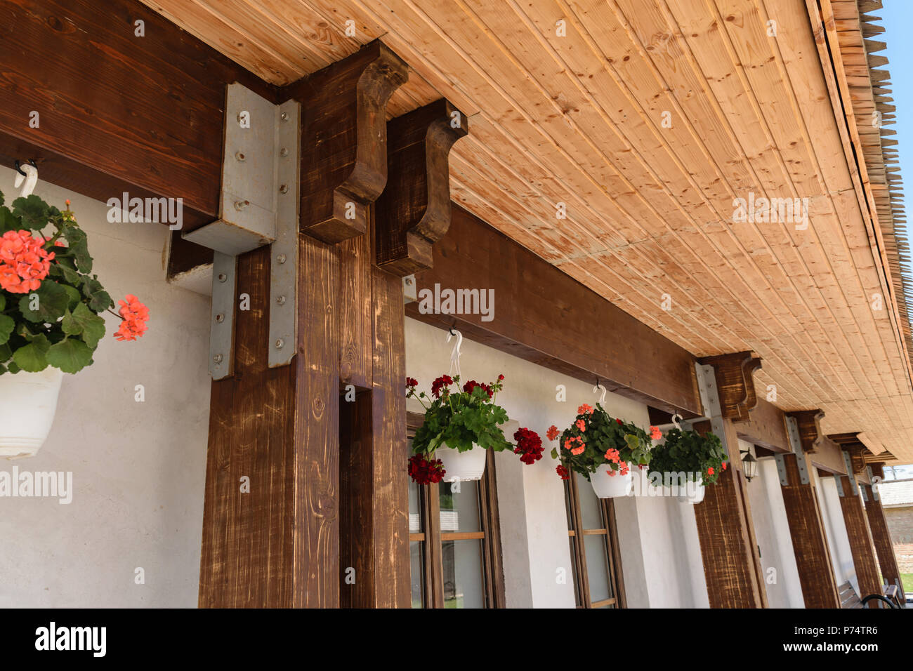 closeup of wood beam and pillar junction professionally connected by metal screw plate. Exterior roof support structure and geranium pots hanging - Stock Image