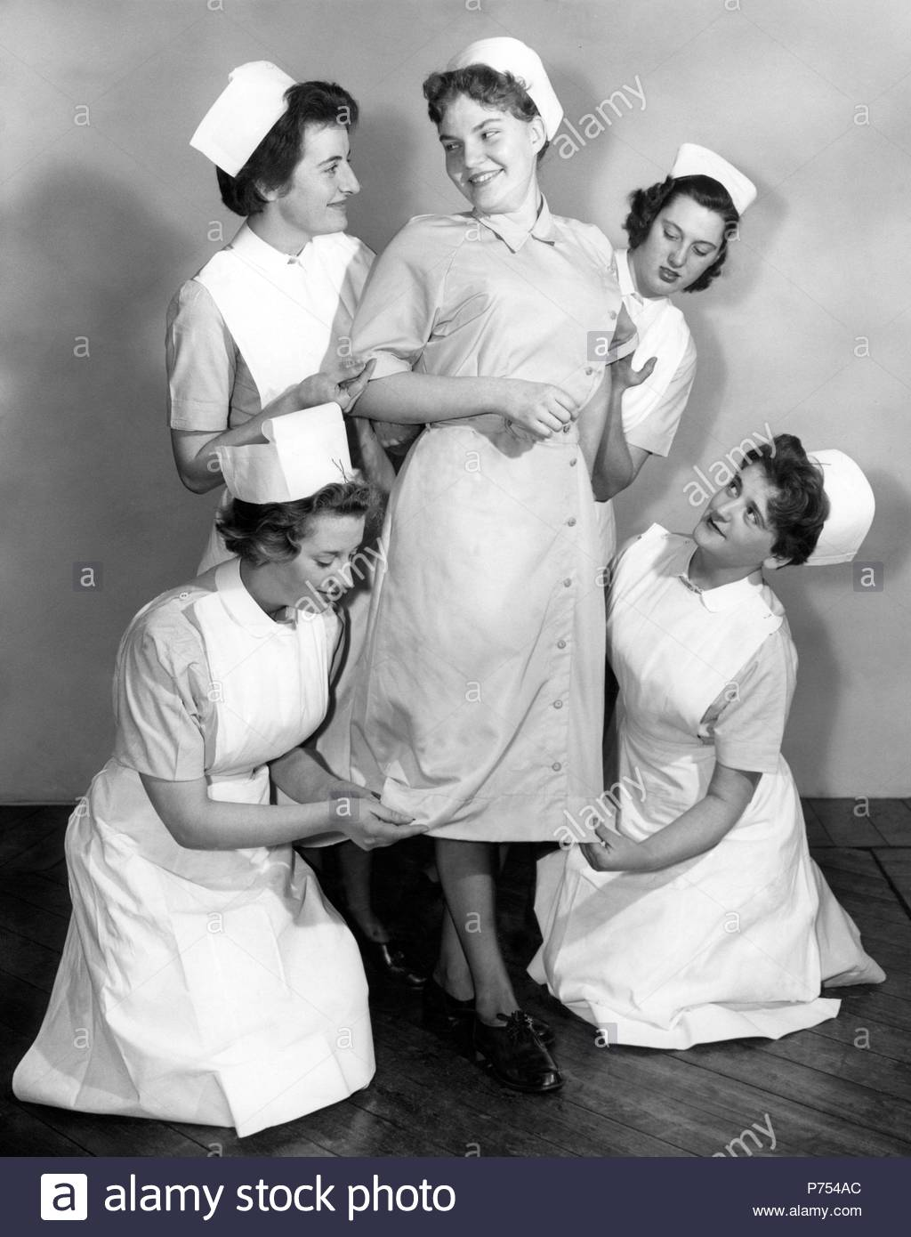 File photo dated 18/12/58 of a new design of uniform being modelled by, then 20-year-old student nurse Gene Williams (centre) at Clatterbridge Hospital, Bebington, Wirral, Cheshire, to be worn by National Health Service (NHS) nurses. - Stock Image