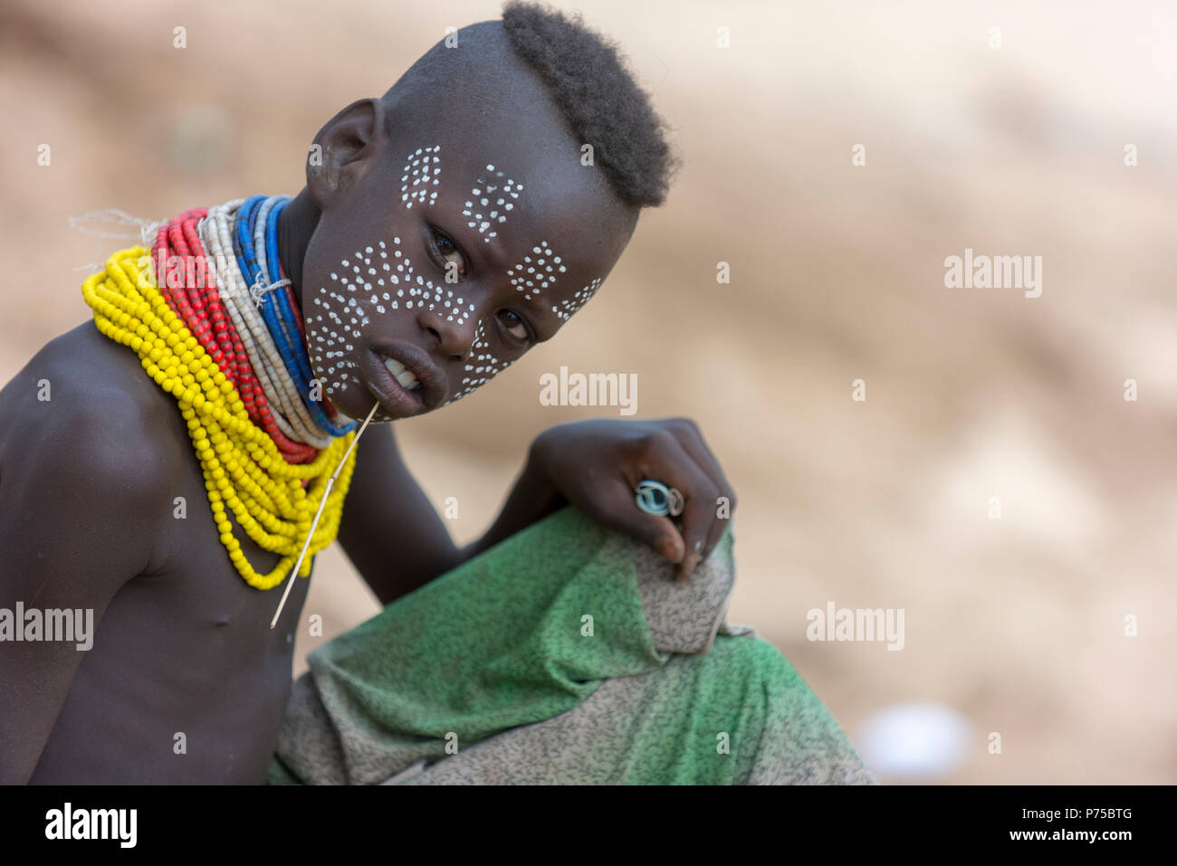 Karo boy poses for a photo.  In his hand is money earned from tourists by posing for such photos. - Stock Image