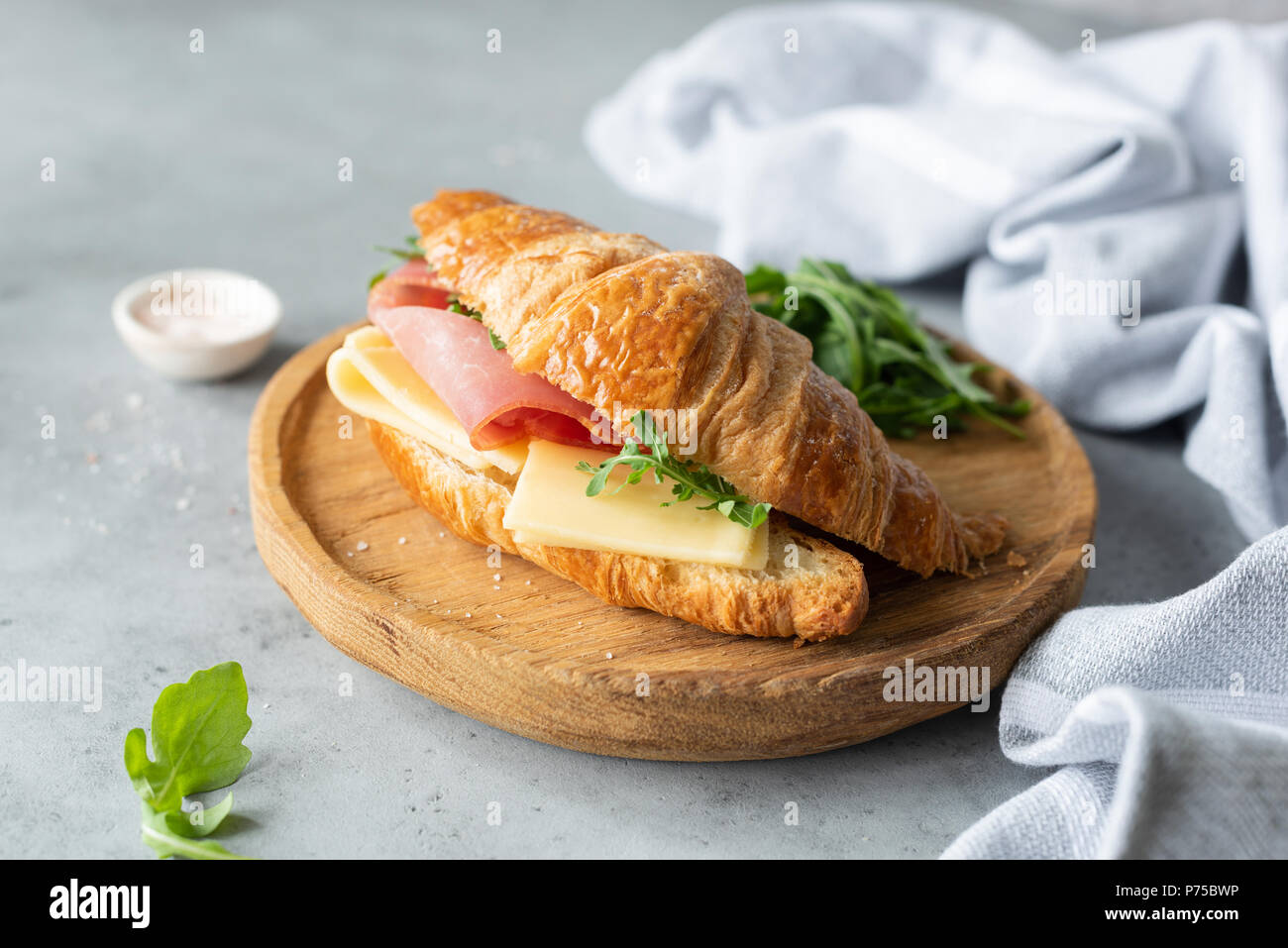 Croissant sandwich with cheese, ham and arugula on wooden cutting board, gray concrete background. Selective focus. Tasty breakfast sandwich or snack - Stock Image
