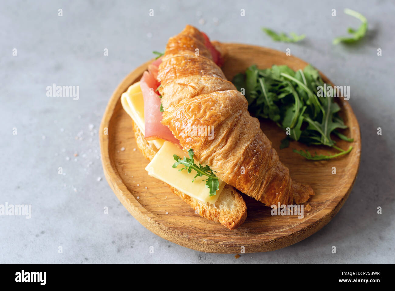Tasty croissant sandwich with ham and cheese on wooden board on grey concrete background. Breakfast, lunch or snack sandwich - Stock Image