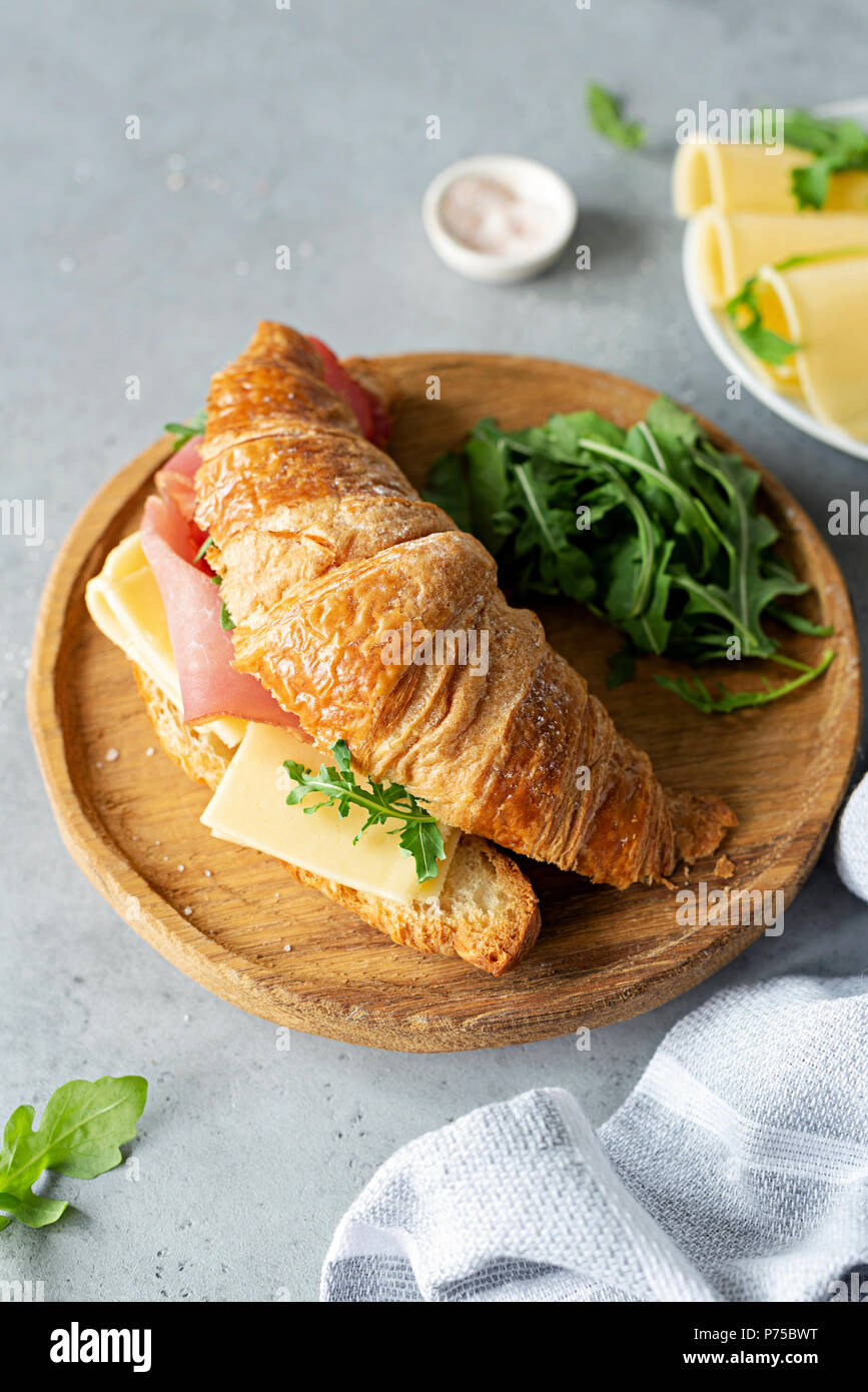 Tasty croissant sandwich with ham and cheese on concrete background. Top view. Breakfast sandwich - Stock Image