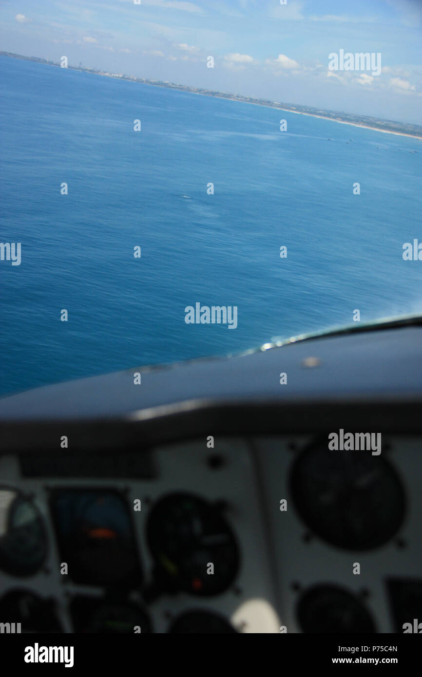 Fishing Boats and a Humpback Whale off the Shore of Ghana, as seen from the Cockpit of an Airplane - Stock Image