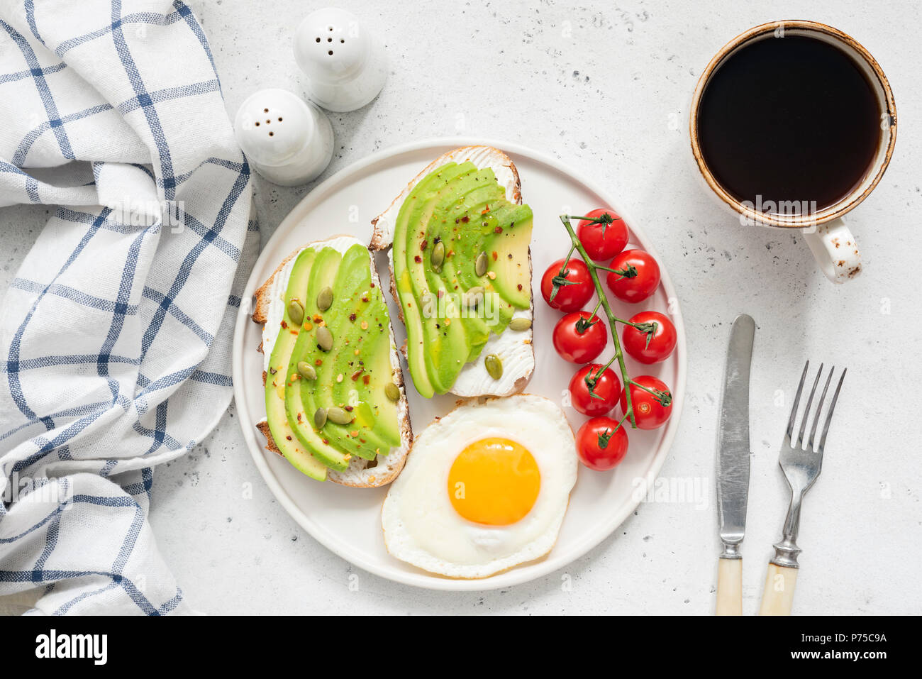 Avocado toast, egg and coffee for breakfast. Top view of healthy breakfast. Two toasts with avocado and cream cheese, sunny side up egg, cherry tomato - Stock Image