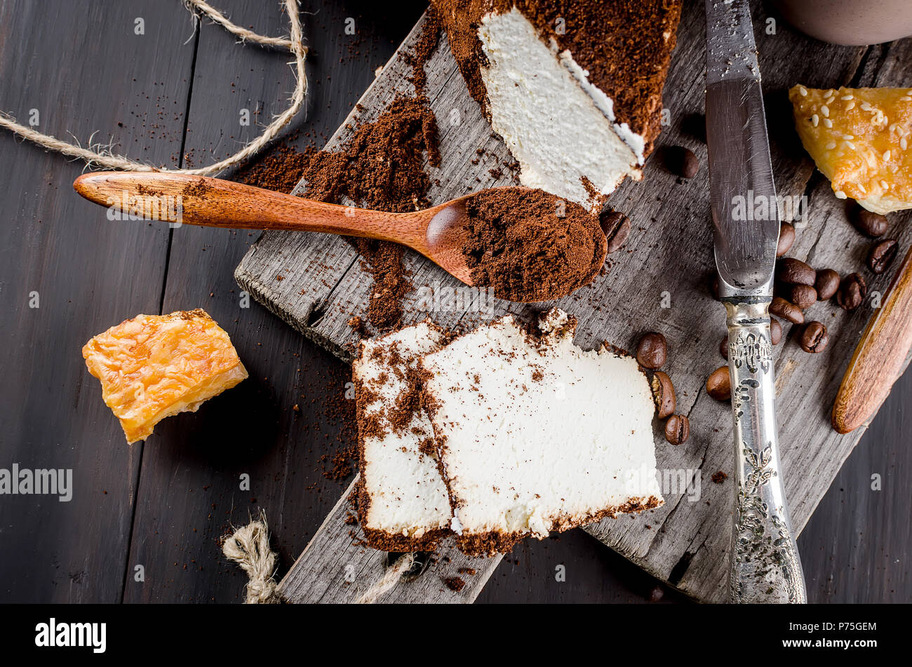 soft homemade cheese wrapped in ground coffee and a cup of coffee with milk breakfast on a wooden table - Stock Image
