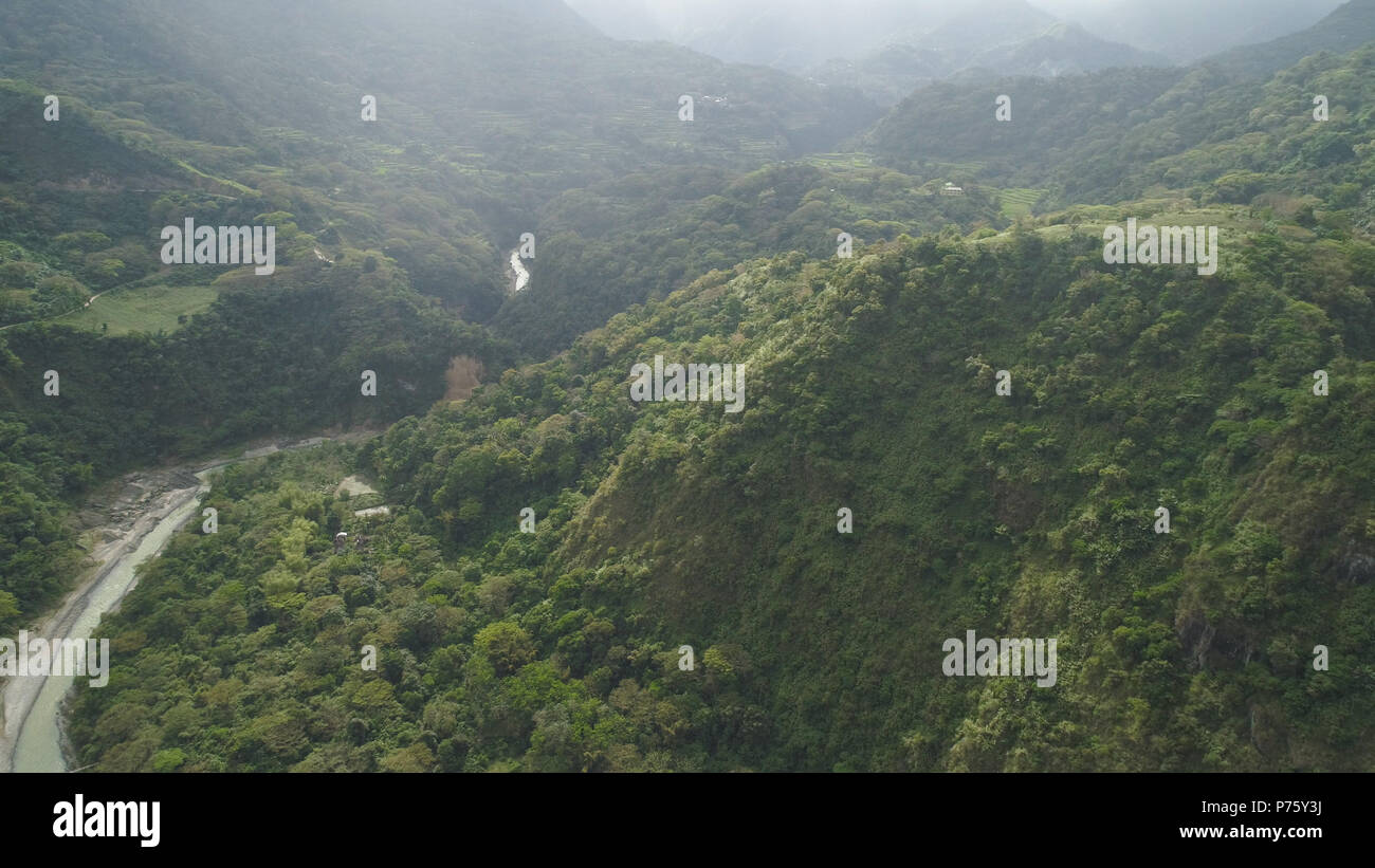 Aerial view of mountain valley with river, rice terraces, farmland in the Philippines, Luzon. Aerial view of mountains covered forest, tree. Cordillera region. Stock Photo