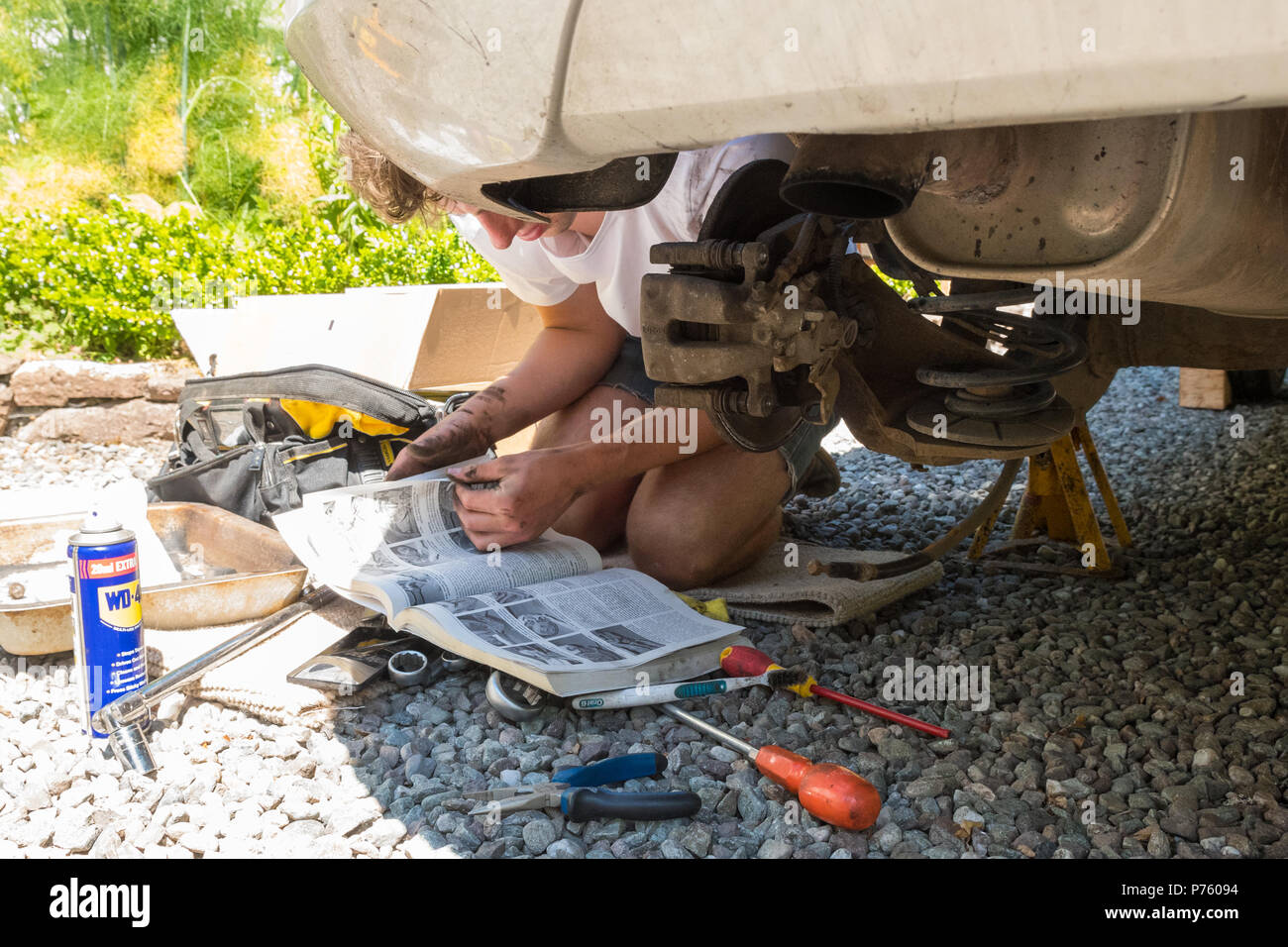 DIY car maintenance and repairs - young man reading Haynes manual as he changes the brake pads, brake disc and brake caliper for the first time - Stock Image