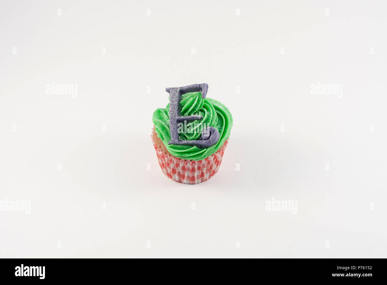 A Cupcake decorated with alice in wonderland - Stock Image