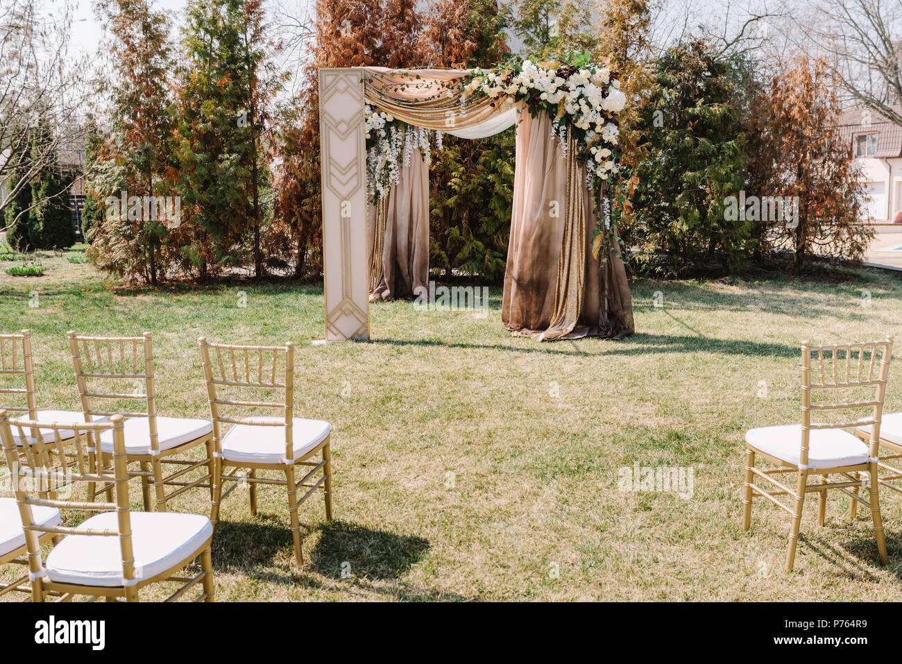 Magnificent wedding arch for a wedding ceremony the square arch magnificent wedding arch for a wedding ceremony the square arch decorated by golden fabric and flowers junglespirit Choice Image