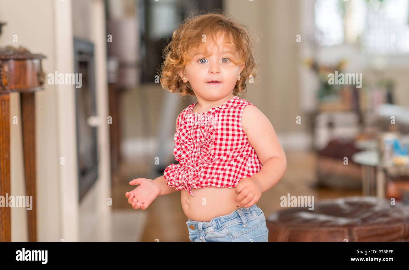 Beautiful blonde child with blue eyes standing showing belly button at home. - Stock Image