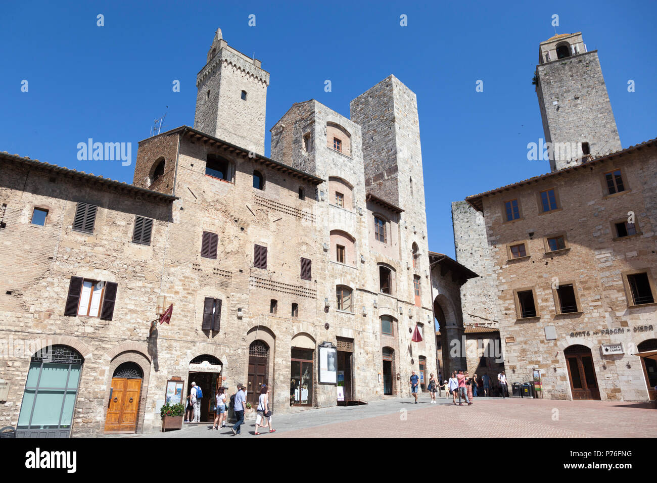 Gently sloping down, the cistern square of San Gimignano (Tuscany)  is encircled with austere residences dating back from century 13 th and 14 th. - Stock Image