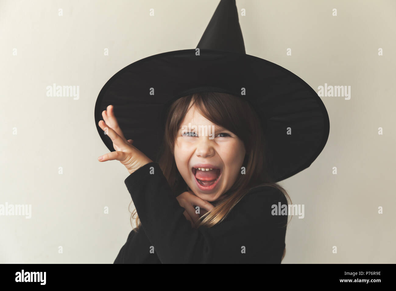 Little grimacing blond European girl in black witch costume over white wall, close-up studio portrait - Stock Image