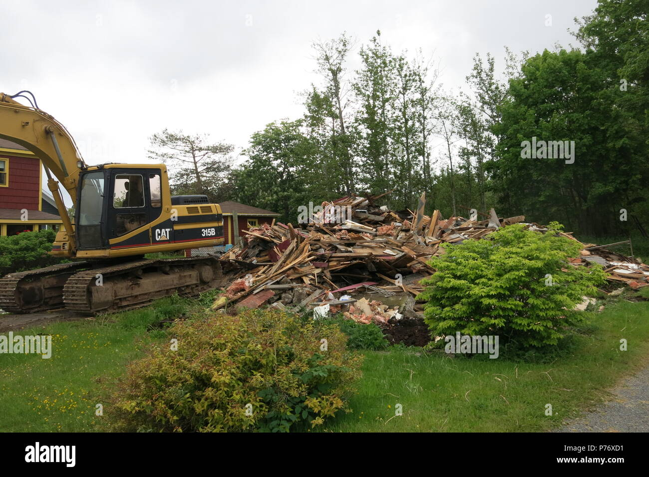 A pile of timbers on this plot is all that remains after the bulldozer has been in to demolish the former dwelling - Stock Image