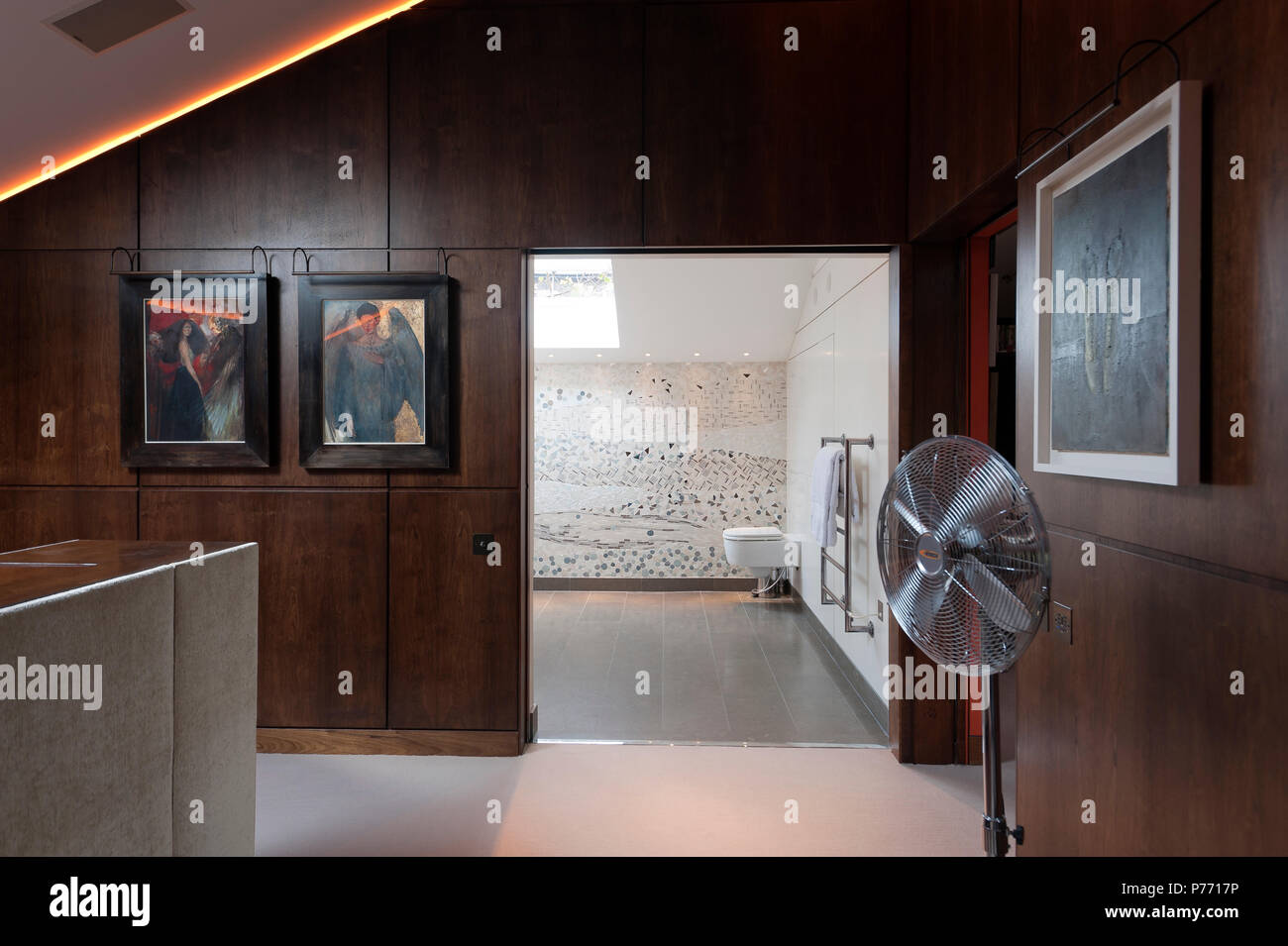 Fan in masculine bedroom by bathroom - Stock Image