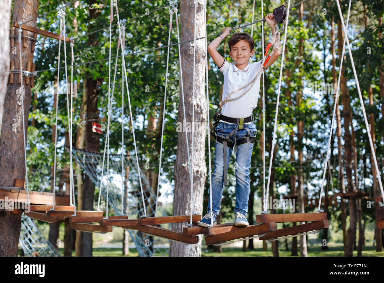 Upbeat preteen boy posing at rope park - Stock Image