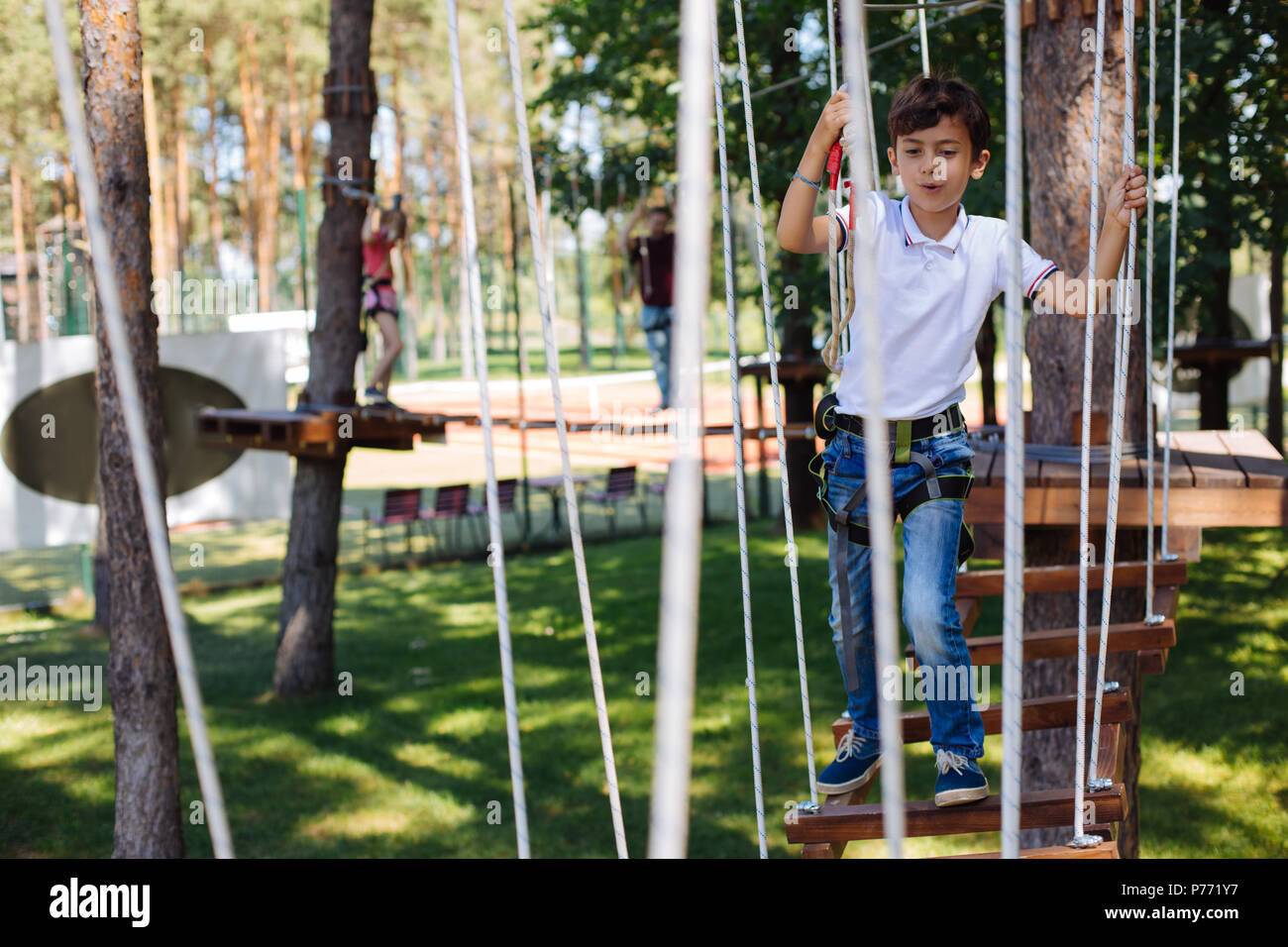 Pleasant preteen boy enjoying himself at rope park - Stock Image