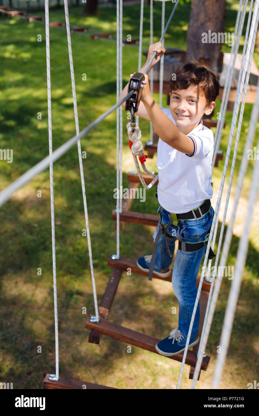 Top view of cheerful preteen boy climbing at rope park - Stock Image